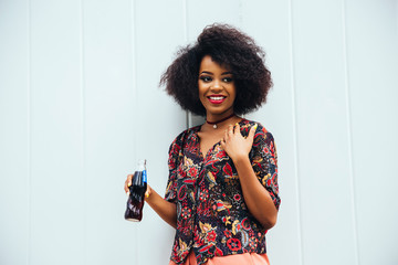 Smiling beautiful afro american girl holding a bottle with drink, dressed in colorful blouse. Standing outdoors.