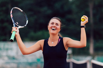 Tennis player. Glad beautiful woman showing happy emotion after winning tennis match, raising racket and ball. Outdoors.
