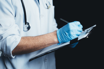 Doctor on a black background in a white robe writes in a folder or notebook