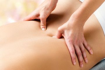 Therapist doing lower lumbar massage on woman.