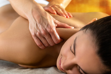 Therapist massaging upper neck and shoulder on woman.
