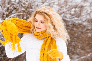 Happy winter blond curly woman in white sweater wrapping herself up in yellow scarf freedom enjoying the cold season. Winter mood concept.