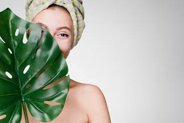cute young girl enjoying spa treatments, holding a green leaf, wearing a towel on her head