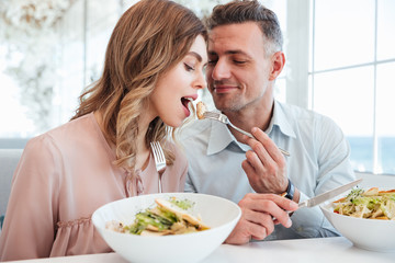 Handsome mature man feeding beautiful woman with salad, while having romantic meal in restaurant on sunny day