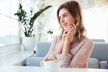 Portrait of a lovely young woman having cup of coffee