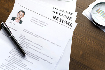 Resume (curriculum vitae, cv) and pen on a written wooden table. Business and staff recruitment.