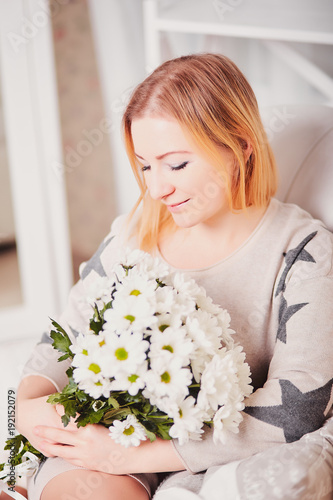 Beautiful Young Woman Sits Tilted Head And Holds A Bouquet Of
