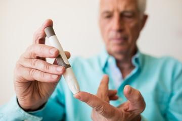 Senior man holding a blood glucose monitor
