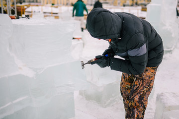 A man makes a sculpture of ice