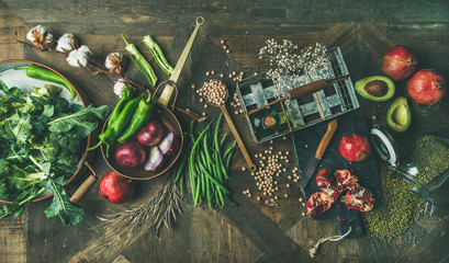 Winter vegetarian or vegan food cooking ingredients. Flat-lay of seasonal vegetables and fruits, beans, cereals, kitchen utencils, dried flowers, olive oil over wooden background, top view