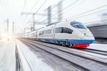 High-speed train rides at high speed in winter around the snowy landscape.
