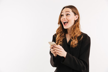 Beautiful curly woman in black jacket looking aside with surprise while holding and using cell phone, isolated over white background