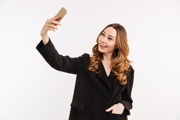 Image of sociable pretty woman in black jacket making selfie and smiling on her cell phone, isolated over white background