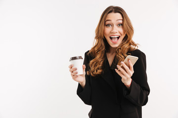 Long-haired brunette woman in black outfit smiling on camera while holding smartphone and takeaway coffee in hands, isolated over white background