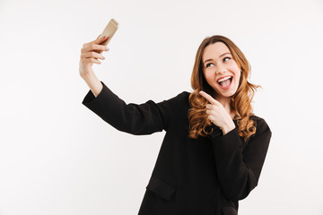 Photo of amusing young woman in black jacket making selfie with smile and pointing finger on mobile phone, isolated over white background