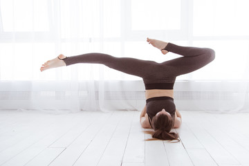 Fitness, stretching workout, attractive mature woman in sportswear working out in sports club, keeping fit, doing shoulderstand exercise, Viparita Karani, Upside-Down Seal pose in class. Lifestyle.