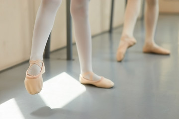 Legs a little ballerina in a pink ballet shoes. Young girl in ballet pose at classical ballet school, cropped image.