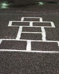 Chalk hopscotch game on asphalt