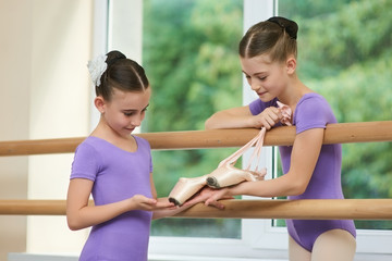 Little ballerina showing slippers to friend. Two beautiful ballerinas with ballet shoes in classical ballet class. Conversation between two little ballet dancers.