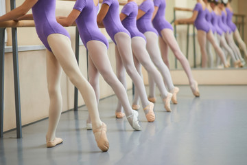 Ballerinas in pointe shoes stretching legs. Group of ballet girls doing stretching exercises before dance lessons. Skills and flexibility of young ballet dancers.
