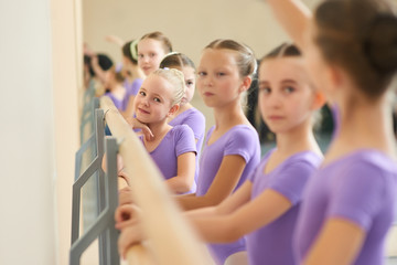 Close up young ballerinas at ballet studio. Young lovely ballet girl near ballet barre. Childrens workouts at ballet school.