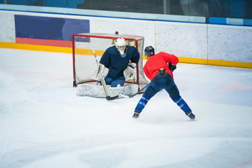 Professional ice hockey player on the ice hockey stadium train together with goalie. Sport photo, edit space, winter game Pyeongchang.