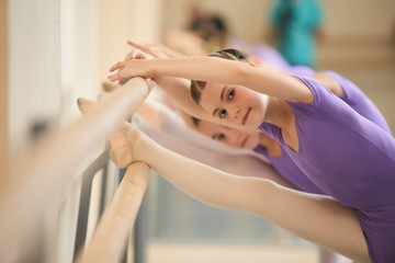 Young ballerina stretching before ballet practice. Ballet girl training her flexibility at ballet barre in hall. Safely technique for stretching.