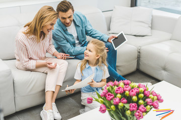 smiling daughter showing parents with digital devices picture at home