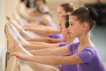 Female ballet dancer practicing in a dance studio. Close up beautiful ballet girl stretching her leg at ballet barre. Helpful tips how to stretch safely.