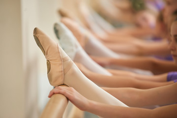 Young ballerina leg in pointe shoes. Close up female ballet dancer leg on barre, cropped image.