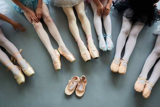 Six ballerinas on the floor, top view. Ballet pointe shoes for little ballet girl. Classical ballet school.