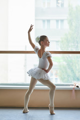 Young ballerina standing in ballet position. Beautiful young ballet girl in white dress posing in ballet dance class. Talented and skillful youth.