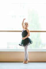 Beautiful ballet girl standing in ballet pose. Pretty young ballerina in black dress posing in ballet class.