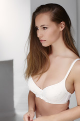 Serious young woman in bra, looking away