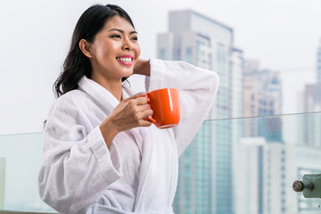 Asian woman in morning front of city skyline drinking coffee