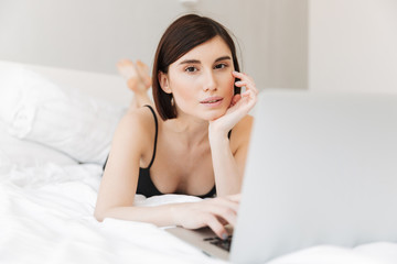 Portrait of a beautiful young woman using laptop computer
