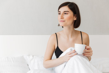 Portrait of a pretty young woman holding cup of coffee