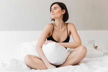 Portrait of a lovely young woman sitting with a pillow