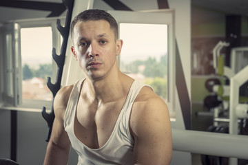Young man fitness portrait, sitting in the gym