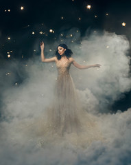 An attractive goddess stands in the clouds in a luxurious, gold, sparkling dress. Whimsical hairstyle. Against the backdrop of a star and space. Artistic Photography