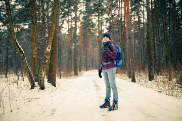 Photo of smiling woman in hat with backpack over winter forest