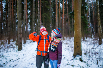 Image of woman and man showing hand forward in winter forest