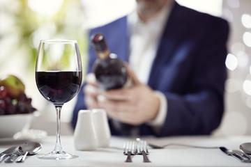 Businessman reading a wine bottle label in restaurant