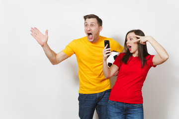 Fun crazy engaged young couple, man, woman doing selfie on mobile phone, football fans cheer up support team with soccer ball isolated on white background. Sport, family leisure, lifestyle concept.