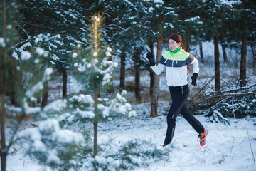 Photo of young athlete woman running in winter forest