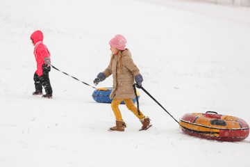 Photo of two girls on walk with tubing in winter park
