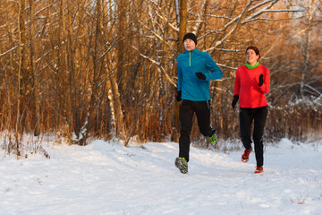 Image of sports woman and man running on winter day