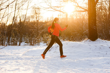 Picture of young brunette in sportswear on morning run in winter