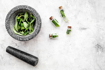 Phytotherapy. Herbs in mortar bowl and in small glasses on grey background top view copy space