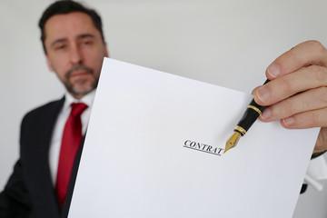 homme tend un contrat et un stylo plume